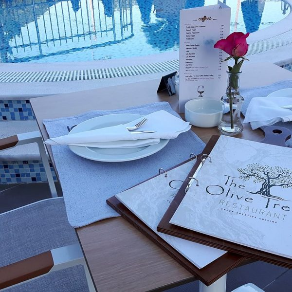 Plates, vase with a rose and menu catalogues at Olive Tree Restaurant in Parga.