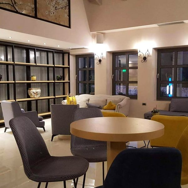 Comfortable chairs, round table and sofas at the lobby of Adams Hotel in Parga.