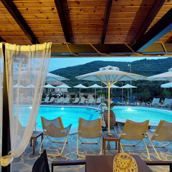 Sun loungers and umbrellas by the pool at Adams Hotel in Parga.