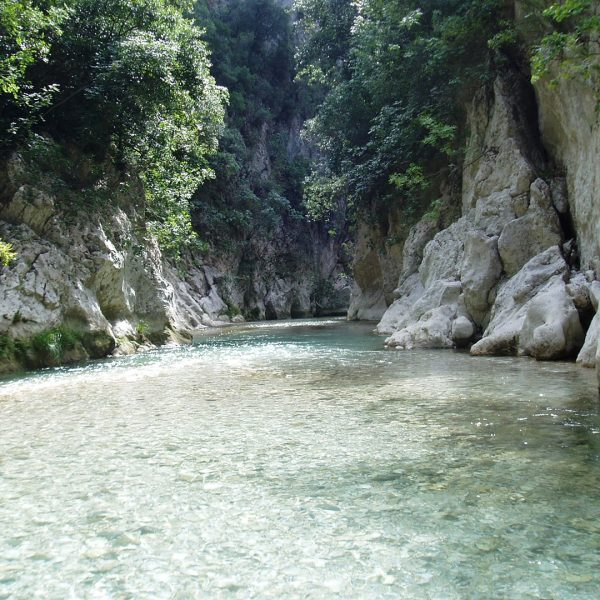 View of Acheron river. White lush rocks and clear light blue water, in Parga.