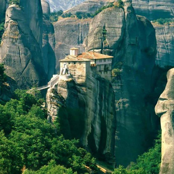 Monastery built on the top of an impressive rock which surrounded by other rocks in Meteora.