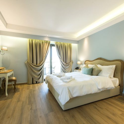 Impressive curtains and double bed with colorful pillows and towels on it at luxury suites Parga.